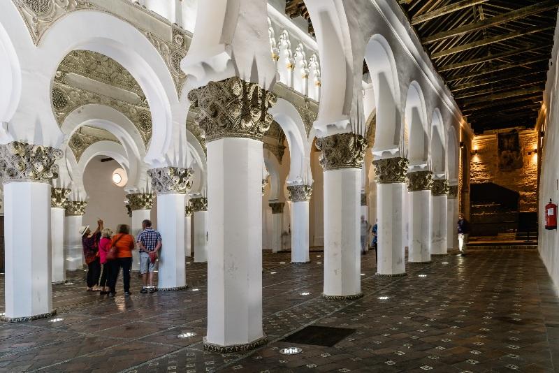Sinangoga de Santa María la Blanca con sus pilares blancos ornamentados contrastan con el techo de madera oscura.