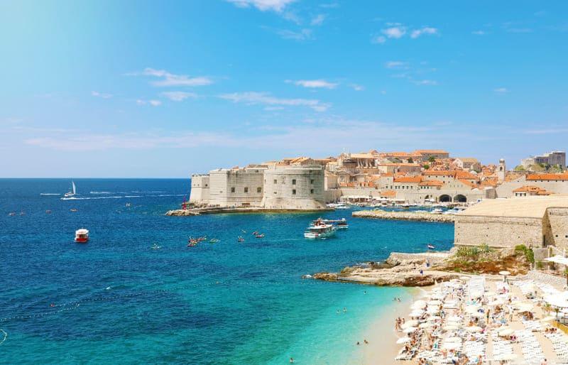 Las playas cristalinas de Dubrovnik y la ciudad vieja de fondo son un lugar perfecto para el turismo